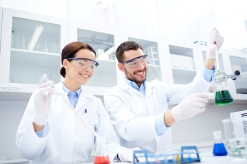 science chemistry technology biology and people concept  young scientists with pipette and flask making test or research in clinical laboratory