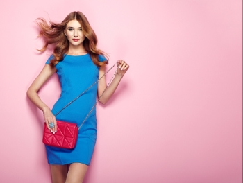 Blonde young woman in elegant blue dress Girl posing on a pink background Jewelry and hairstyle Girl with red handbag Fashion photo