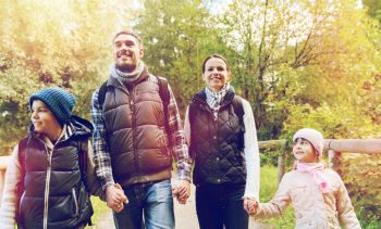 travel tourism hike and people concept  happy family with backpacks hiking in woods happy family with backpacks hiking