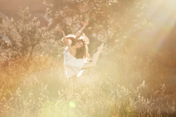 The ballerina doingis arabesk at the meadow In the white dress At the nature background with the rays of sunset