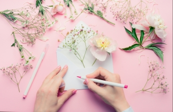 Female hands write with pencil on opened envelop with flowers arrangement Florist decoration equipment on pink table background top view Invitati