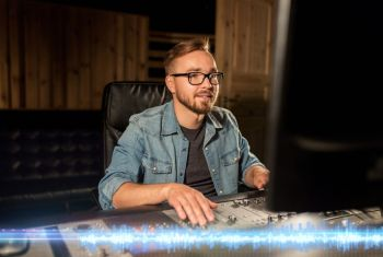 music technology and people concept  man at mixing console in sound recording studio man at mixing console in music recording studio