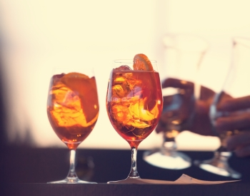 Two glasses of spritz cocktail at sunset