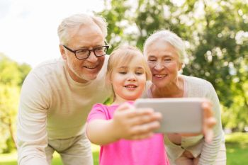 family generation and people concept  happy smiling grandmother grandfather and little granddaughter taking selfie by smartphone at park senior gr