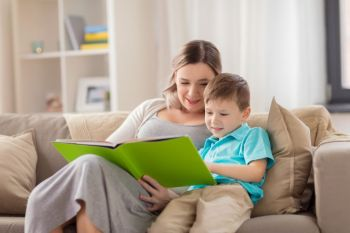 people and family concept  happy mother and little son reading book on sofa at home happy family reading book at home