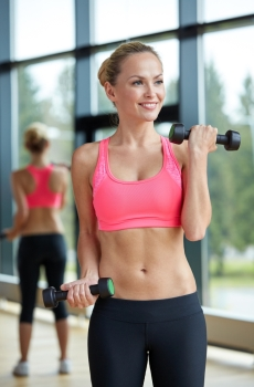 sport fitness training weightlifting and people concept  young sporty woman with dumbbells flexing biceps in gym