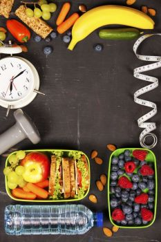 Health  Fitness Food in lunch boxes measuring tape and alarm clock on wooden board Diet food health and fitness concept