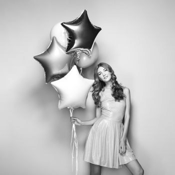 Beautiful Young Woman with Balloons on a White Background Birthday and Party Girl in Gray Dress at the festival Black and White photo