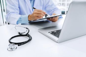 doctor working on laptop with stethoscope and paper clipboard selective focus