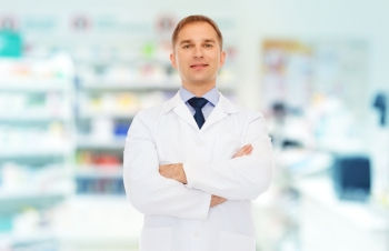 medicine pharmacy people health care and pharmacology concept  smiling male pharmacist in white coat over drugstore background