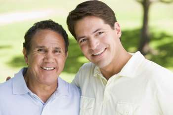 Two men standing outdoors smiling