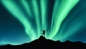Northern lights and silhouette of standing man with raised up arms on the mountain in Norway Aurora borealis and happy man Sky with stars and green