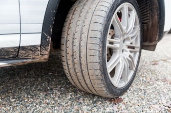 transport driving and motor vehicle concept  close up of dirty car wheel on ground