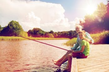 family generation summer holidays and people concept  happy grandfather and grandson with fishing rods on river berth grandfather and grandson fis