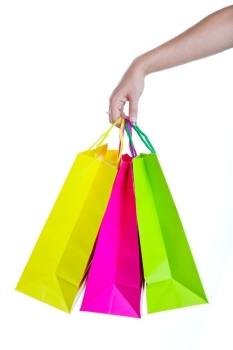 Shopper holding shopping bags in bright spring colors Shot on white background