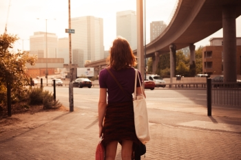 A young woman is walking by the side of a busy road on a sunny afternoon
