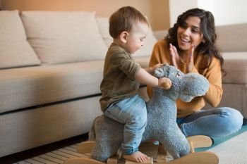 Baby boy playing with a rocking horse with mom s help