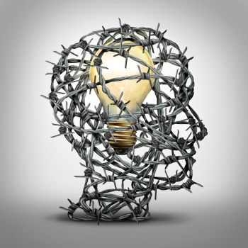 Protect your idea business thinking concept as a group of barbed wire shaped as a human head with an illuminated light bulb inside as a security and t