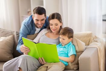 people and family concept  happy mother father and little son reading book on sofa at home happy family reading book at home