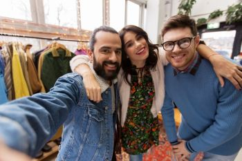 shopping fashion and people concept  happy smiling friends taking selfie at vintage clothing store friends taking selfie at vintage clothing store