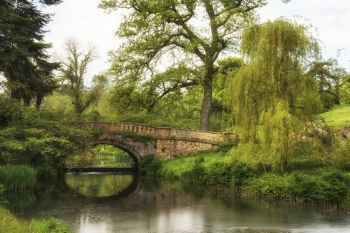 Stunning landscape image of old medieval bridge over river with mirror like reflections