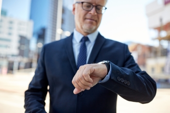business and people concept  senior businessman checking time on his wristwatch in city senior businessman with wristwatch on city street