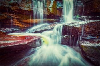 Vintage retro effect filtered hipster style image of tropical waterfall Popokvil Waterfall Bokor National Park Cambodia