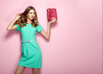 14934baeb7b Blonde young woman in elegant green dress Girl posing on a pink background  Jewelry and hairstyle