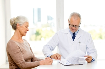 medicine age health care and people concept  senior woman and doctor meeting in medical office