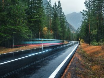 Blurred car on the road in spring forest in rain Perfect asphalt mountain road in overcast rainy day Roadway pine trees in alps Transportation Hi