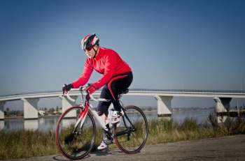 Man on road bike riding down open country road bridge on background