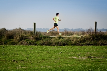 Male runner at sprinting speed training for marathon outdoors on country landscape
