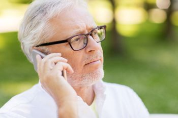 technology senior people and communication concept  close up of sad old man in glasses calling on smartphone at summer park sad senior man in glas