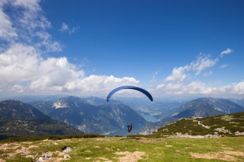Parachute jumping extreme sport Paraglider flying over mountains in summer day