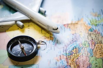 selective focus of miniature tourist on compass over map with plastic toy airplane abstract background to travel concept