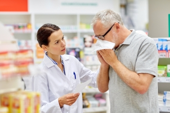 medicine pharmaceutics health care and people concept  pharmacist and sick senior man with flu blowing nose at pharmacy