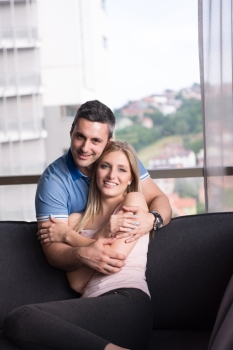 young handsome couple enjoys hugging on the sofa in their luxury home villa