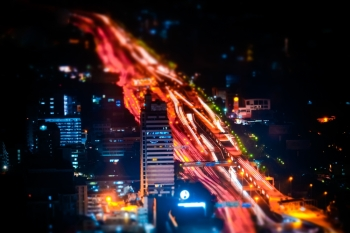Tilt shift blur effect Futuristic night cityscape aerial view panorama with illuminated skyscrapers and city traffic across streets Bangkok Thailan