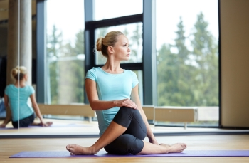 fitness sport training and lifestyle concept  smiling woman stretching leg on mat in gym