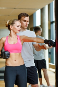 sport fitness lifestyle and people concept  smiling woman with personal trainer boxing in gym