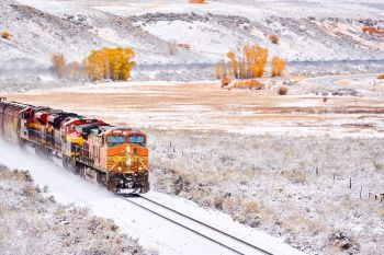 Train transporting tank cars Season changing first snow and autumn trees Rocky Mountains Colorado USA