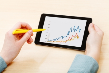 businessman touches by pen of tablet PC with graph on screen at office table