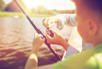 family generation summer holidays and people concept  boy and grandfather with fishing rod or spinning on river or lake berth boy and grandfather