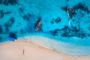 Aerial view of the fishing boats in clear azure water at sunrise in summer Top view from drone of boat blue sea sandy beach walking people Indian