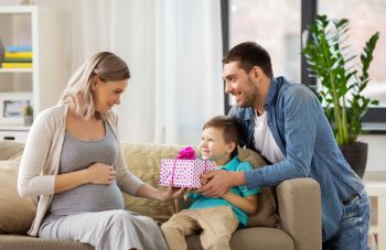 family holidays and greetings concept  father and little son giving present to happy pregnant mother at home family giving present to pregnant moth