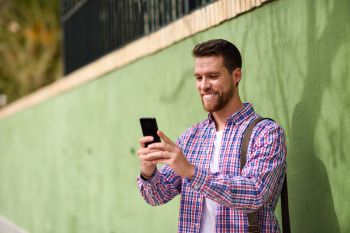 Young man looking at his smart phone in urban background Lifest Young man looking at his smart phone and smiling in urban background Guy wearing ca