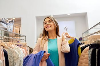 shopping fashion sale and people concept  happy young woman with clothes on hangers in mall or clothing store happy young woman choosing clothes i