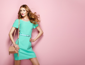 Blonde young woman in elegant green dress Girl posing on a pink background Jewelry and hairstyle Girl with handbag Fashion photo