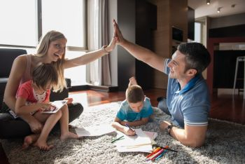 Happy Young Family Playing Together at home on the floor using a tablet and a children s drawing set