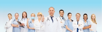 medicine profession teamwork and healthcare concept  international group of smiling medics or doctors with clipboard and stethoscopes with showing